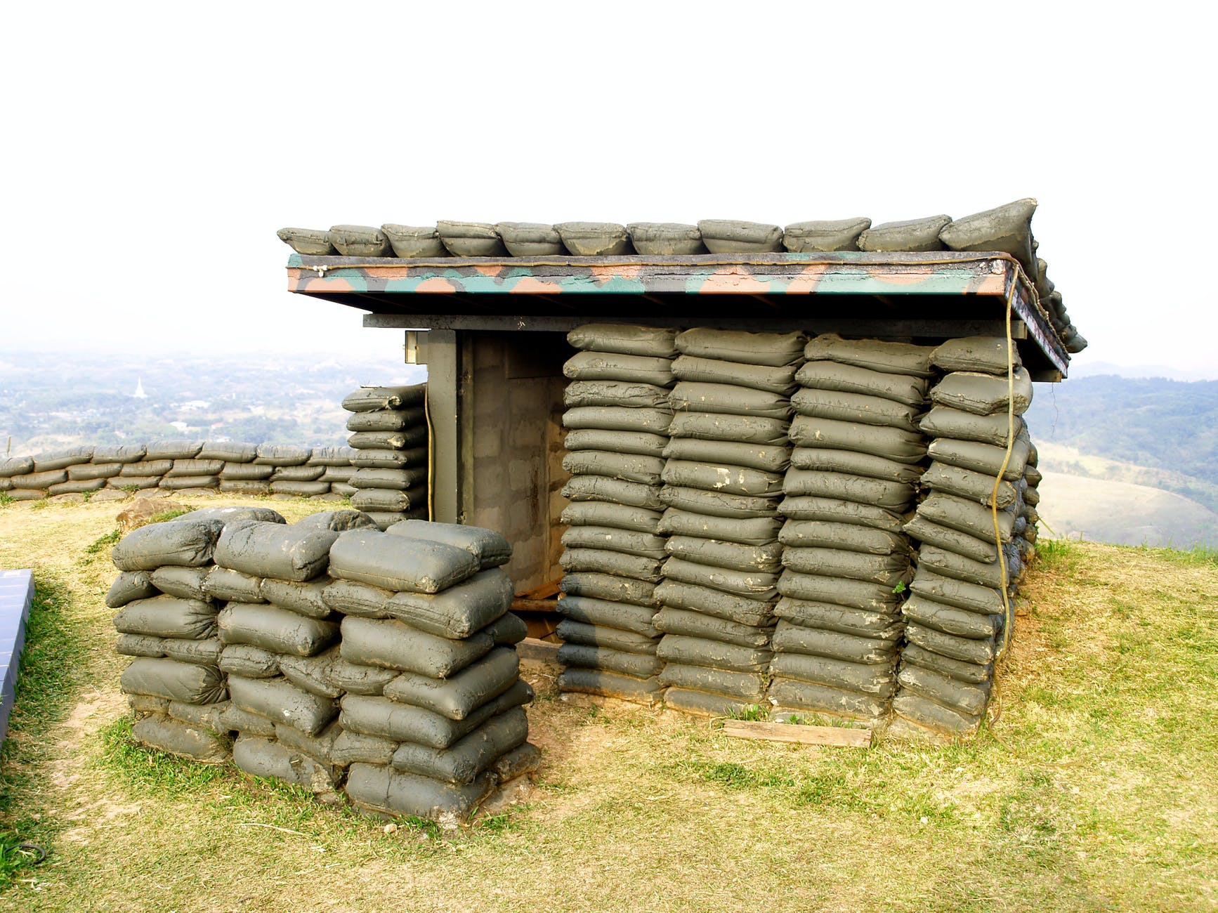 A military looking bunker covered in sacks of concrete and painted dark green