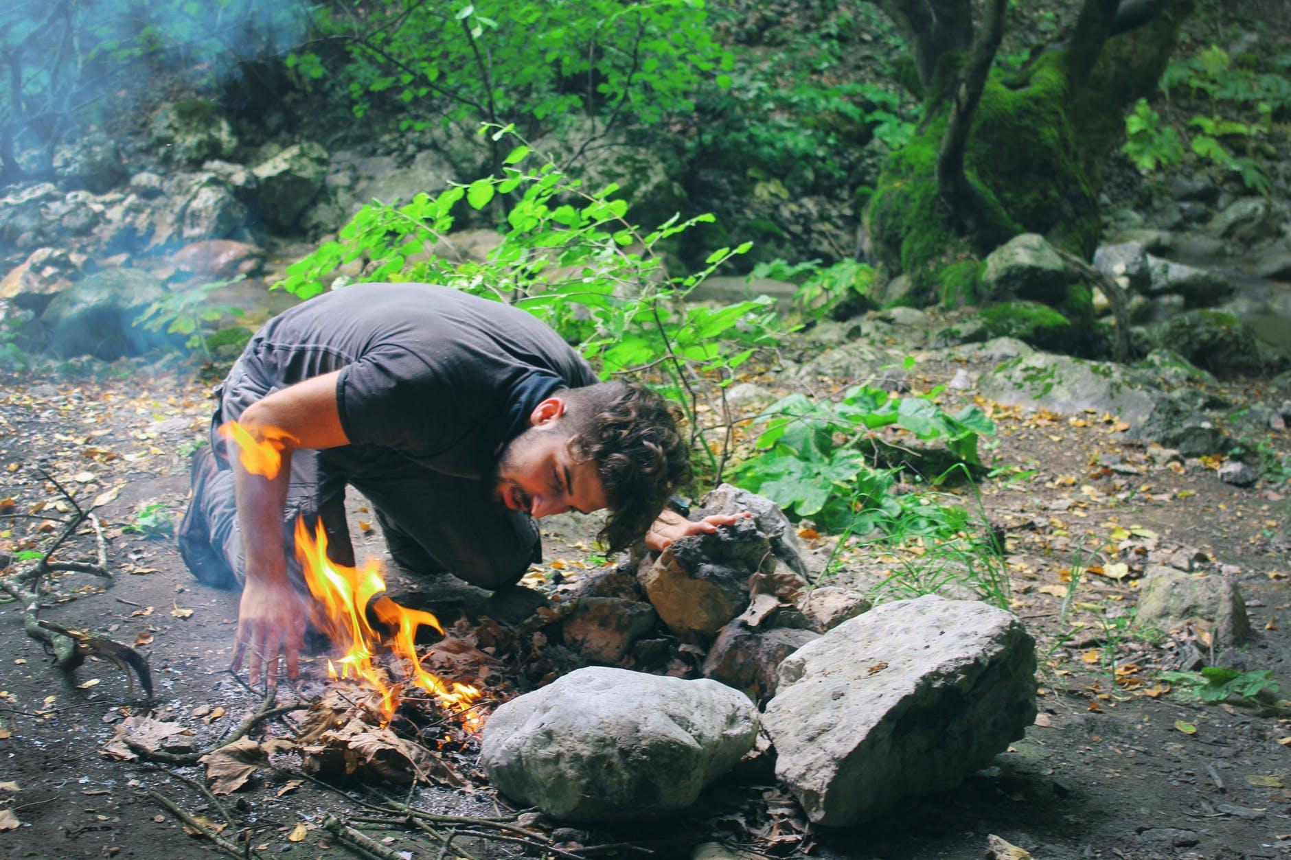 A photo of a man lighting a camp fire